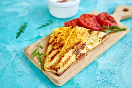 Grilled pike fillet with tomatoes on wooden board on blue background. Grilled seafood. Barbecue fish. Copy space. Healthy food.