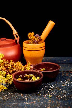 Cup of herbal tea - tutsan, sagebrush, oregano, helichrysum, lavender near brown teapot on dark wooden background. Herbal tea. Dry Herbs and flowers, herbal medicine. Фото со стока