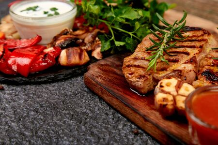 Grilled meat. Steak pork grill on wooden cutting board with a variety of grilled vegetables on black background. Copy space.
