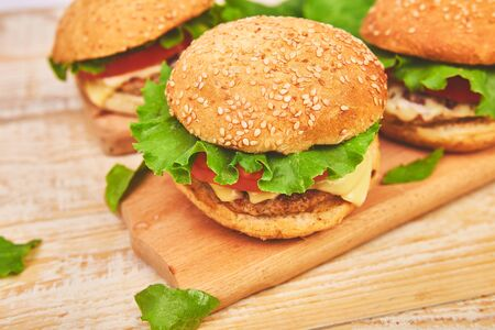 Craft beef burger on wooden table on light background. Street food, fast food. Homemade juicy burgers with cheese and on the wooden table. Copy space. Фото со стока