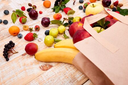Paper bag of different health fruits food on wooden background. Top view. Flat lay Beige canvas grocery bag fallen over while dropping fruits.