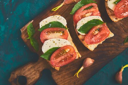 Caprese bruschetta toasts on cutting board. Bruschetta with tomatoes, mozzarella cheese and basil on a green background. Traditional italian appetizer or snack, antipasto Фото со стока