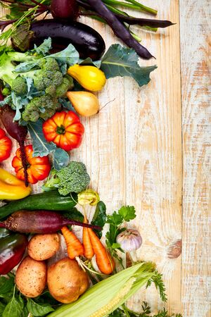 Fresh colorful organic vegetables from above. Top view, flat lay. Different vegetables for eating healthy on wooden background. Clean eating food frame. Copy space. Vegetarian, vegan.