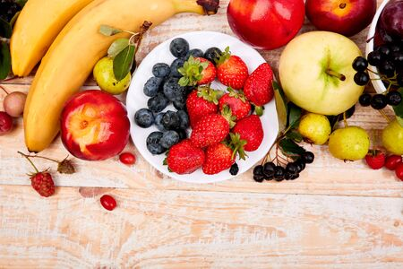 Flat lay of fruits over white wooden background, top view. Vegetarian, vegan, dieting, clean eating, weight loss ingredients. Summer fruit food background. Copy space.