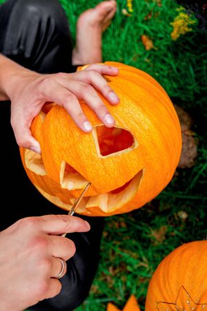A close up of man's hand who cuts with knife a pumpkin as he prepares a jack-o-lantern. Halloween. Decoration for party. Banco de Imagens - 128664085