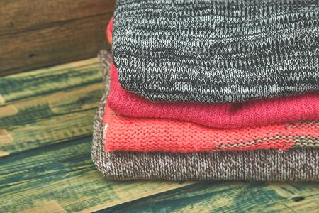 Stack of cozy knitted sweaters. A pile of warm sweaters on a wooden table on green rustic background. Autumn and winter clothes. Copy space.