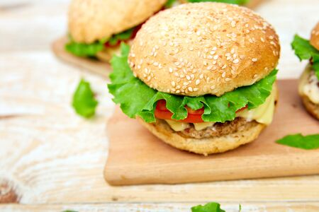 Craft beef burger on wooden table on light background. Street food, fast food. Homemade juicy burgers with cheese and on the wooden table. Copy space. Stockfoto