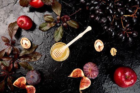 Autumn frame background. Autumn food still life with season fruits grape and figs, honey on a black table. Thanksgiving day. Reklamní fotografie