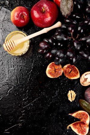 Autumn harvest frame background. Autumn food still life with season fruits grape and figs, honey on a black table. Thanksgiving day.