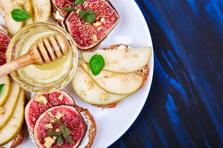 Bruschetta and Crostini with pear, ricotta cheese, honey, figs, nuts and herbs. Breakfast toasts or snack sandwiches. Antipasto. Italian food. Top view. Copy space.