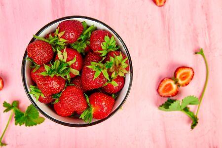Ripe red strawberries on pink table, Strawberries in bowl. Fresh strawberries. Beautiful strawberries. Diet food. Healthy, vegan. Top view. Flat lay. Banco de Imagens - 131017625