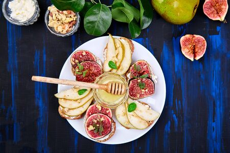 Bruschetta and Crostini with pear, ricotta cheese, honey, figs, nuts and herbs. Breakfast toasts or snack sandwiches. Antipasto. Italian food. Top view. Copy space. Banco de Imagens - 131017627