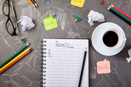 Goals as memo on notebook with idea, crumpled paper, cup of coffee over on grey background. Top view. Banco de Imagens - 131017628