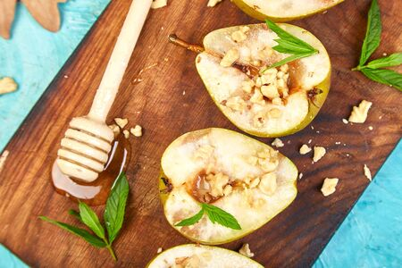 Tasty roast pears with honey and walnuts on wooden board on blue background table. Top view. Flat lay. Copy space. Banco de Imagens - 131017632