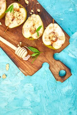 Tasty roast pears with honey and walnuts on wooden board on blue background table. Banco de Imagens - 131017635