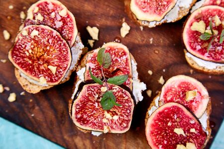 Bruschetta or ctostini with cottage cheese, figs and honey. Sandwich with figs and goat cheese. Banco de Imagens - 131017631