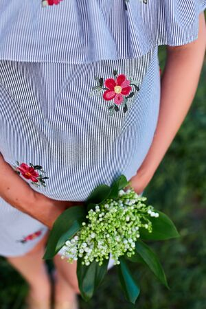 Pregnant woman holding her belly and flower, outdoor. Pregnancy, motherhood and happy future mother concept Banco de Imagens - 131093958