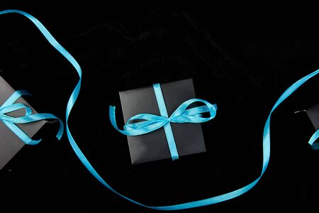 Luxury black gift boxes with blue ribbon on shine black background. Christmas, birthday party presents. Father Day. Flat lay. Copy space. Top view. Banco de Imagens - 131393729