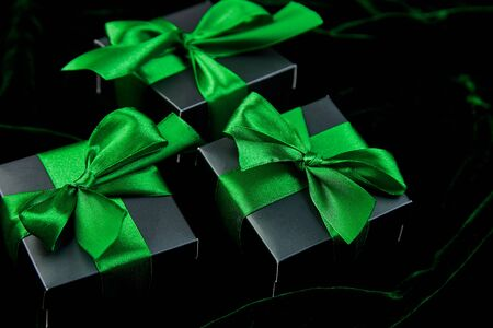 Luxury black gift boxes with green ribbon on shine velvet background. Christmas, birthday party presents. Father Day. Flat lay. Copy space. Top view. Banco de Imagens - 131393784