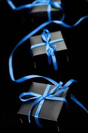 Luxury black gift boxes with blue ribbon on shine black background. Christmas, birthday party presents. Father Day. Flat lay. Copy space. Top view. Banco de Imagens - 131393459