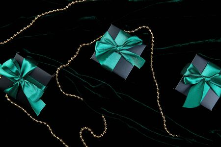 Luxury black gift boxes with green ribbon on shine velvet background. Christmas, birthday party presents. Father Day. Flat lay. Copy space. Top view. Banco de Imagens - 131439061