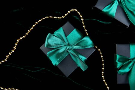 Luxury black gift boxes with green ribbon on shine velvet background. Christmas, birthday party presents. Father Day. Flat lay. Copy space. Top view. Banco de Imagens - 131439062