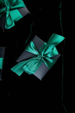 Luxury black gift boxes with green ribbon on shine velvet background. Christmas, birthday party presents. Father Day. Flat lay. Copy space. Top view. Banco de Imagens - 131393862