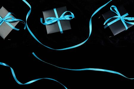 Luxury black gift boxes with blue ribbon on shine black background. Christmas, birthday party presents. Father Day. Flat lay. Copy space. Top view. Banco de Imagens