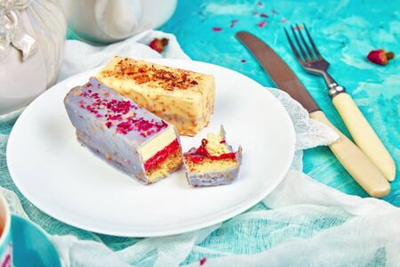 Mini Mousse Cake with chocolate, covered with blue spray and decorated with pink roses with cups of tea on blue background. Banco de Imagens - 131394448