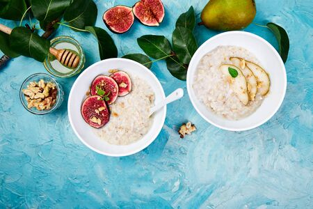 Healthy breakfast. A bowls  of porridge with pears slices and walnuts and porridge with figs on blue background. Two bowls. Flat lay. Copy space. Top view. Banco de Imagens - 131394602