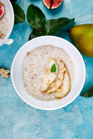Healthy breakfast. A bowl of porridge with pears slices and walnuts on blue background. Flat lay. Copy space. Top view. Banco de Imagens - 131394088