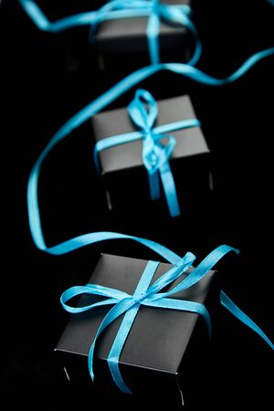 Luxury black gift boxes with blue ribbon on shine black background. Christmas, birthday party presents. Father Day. Flat lay. Copy space. Top view. Banco de Imagens - 131394534