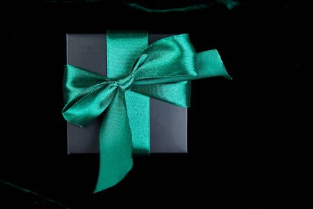 One luxury black gift boxe with green ribbon on shine velvet background. Christmas, birthday party presents. Father Day. Flat lay. Copy space. Top view. Banco de Imagens - 131394814