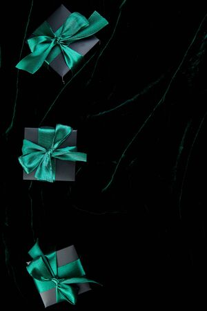 Luxury black gift boxes with green ribbon on shine velvet background. Christmas, birthday party presents. Father Day. Flat lay. Copy space. Top view. Banco de Imagens - 131394424
