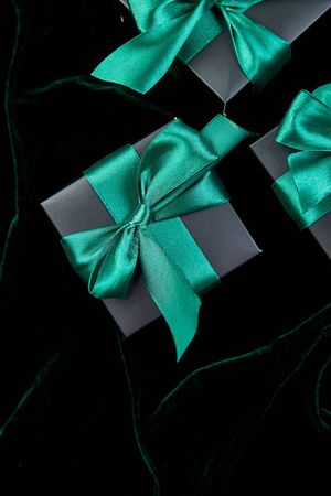 Luxury black gift boxes with green ribbon on shine velvet background. Christmas, birthday party presents. Father Day. Flat lay. Copy space. Top view. Banco de Imagens - 131394211