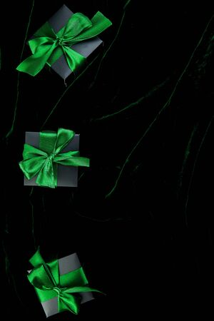 Luxury black gift boxes with green ribbon on shine velvet background. Christmas, birthday party presents. Father Day. Flat lay. Copy space. Top view. Banco de Imagens - 131394667
