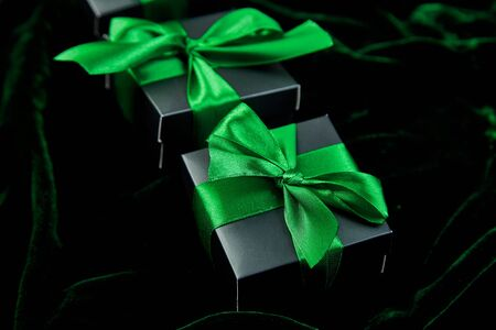 Luxury black gift boxes with green ribbon on shine velvet background. Christmas, birthday party presents. Father Day. Flat lay. Copy space. Top view. Banco de Imagens - 131394386