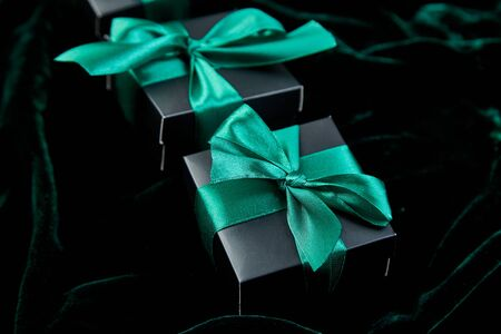 Luxury black gift boxes with green ribbon on shine velvet background. Christmas, birthday party presents. Father Day. Flat lay. Copy space. Top view. Banco de Imagens - 131394893