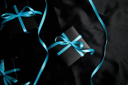 Luxury black gift boxes with blue ribbon on shine black background. Christmas, birthday party presents. Father Day. Flat lay. Copy space. Top view. Banco de Imagens - 131439067