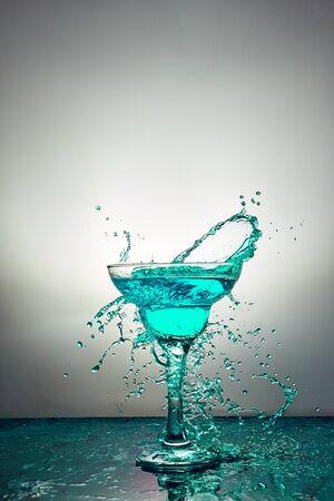 Glass with blue champagne or alcohol drink cocktail, martini glasses. Pouring. Splash. Levitation Banco de Imagens - 131492954