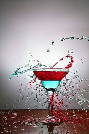 Glass with blue and yellow champagne or alcohol drink cocktail, martini glasses. Pouring. Splash. Levitation 版權商用圖片