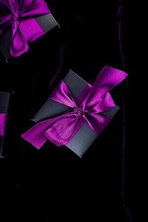 Luxury black gift boxes with purple ribbon on shine velvet background Banco de Imagens - 131492953