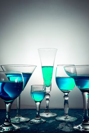 Many different glasses with blue champagne or alcohol drink cocktail, martini glasses. Pouring. Splash. 版權商用圖片