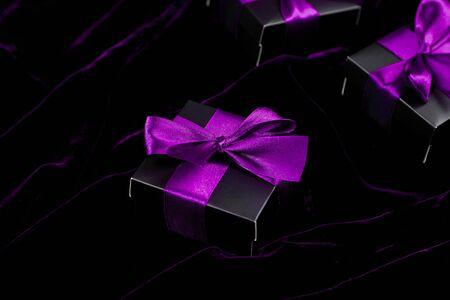 Luxury black gift boxes with purple ribbon on shine velvet background. Banco de Imagens - 131492960