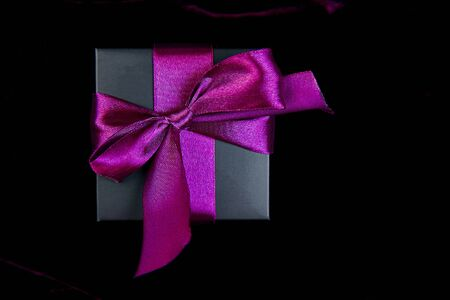 One luxury black gift boxe with green ribbon on shine velvet background. Christmas, birthday party presents. Father Day. Flat lay. Copy space. Top view.