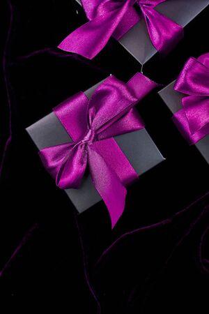 Luxury black gift boxes with purple ribbon on shine velvet background. Banco de Imagens