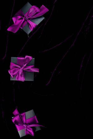 Luxury black gift boxes with purple ribbon on shine velvet background. Banco de Imagens - 131492961