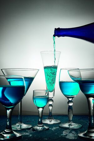 Many different glasses with blue champagne or alcohol drink cocktail, martini glasses. Pouring from bottle. Splash.
