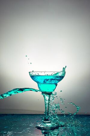 Glass with blue champagne or alcohol drink cocktail, martini glasses. Pouring. Splash. Levitation