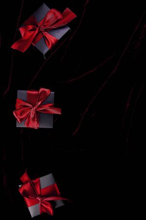 Luxury black gift boxes with red ribbon on shine velvet background